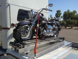 Picture Of Motorcycle Loader behind the cab of a Freightliner RV Hauler